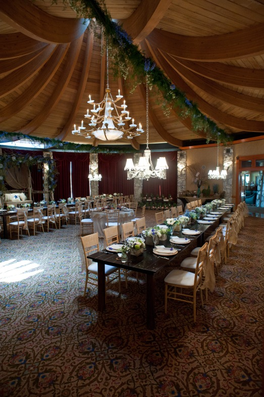Florals and greens strung across the ceiling to hang chandeliers off of by Layers of Lovely Floral Design