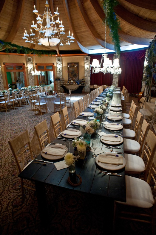Long wood tables lined with flowers and chandeliers above