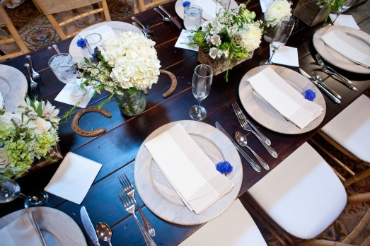 Long wood tables with wood chargers and rustic florals by Layers of Lovely Floral Design