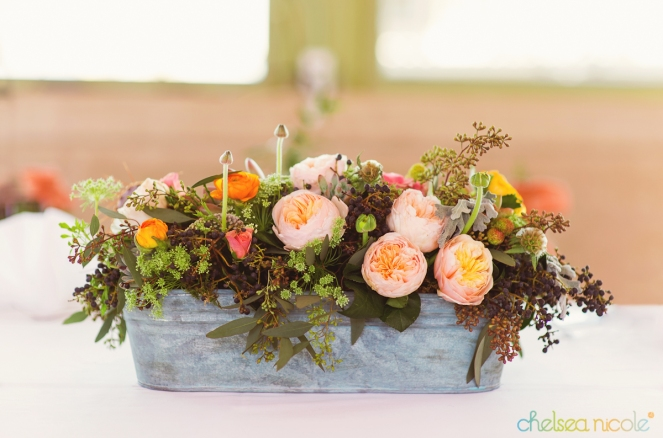 Patina bucket filled with peach and coral flowers by Layers of Lovely