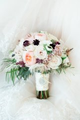 Bridal bouquet of roses, garden roses, chocolate cosmos, astilbe, anemones and touches of feathers.